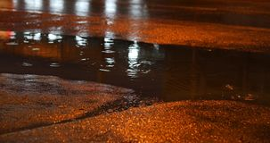 Night street in the rainy weather day with car driving on asphalt road. Night street in the rainy weather day, rain drop on puddle water with car driving on stock video footage