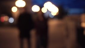 Night Street and silhouettes of people, blurred background. Blur. Couple walking in the city at night.  stock video