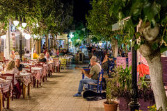 Night street with tavernas full of tourists and street musicans at Paleochora town in west part of Crete island. Royalty Free Stock Image