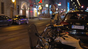 Night street in Vienna, Austria. VIENNA, AUSTRIA - APRIL 26, 2016: View to night street with parked cars and motorbike. Man on the bike passing by stock footage