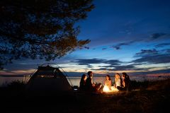 Night summer camping on shore. Group of young tourists around campfire near tent under evening sky. Night summer camping on lake shore. Group of five young royalty free stock photo
