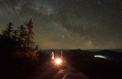 Night summer camping in the mountains under night starry sky. Happy couple hikers having a rest together, standing beside campfire on the top of big boulder in royalty free stock photos