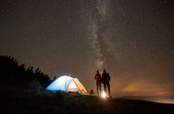 Night summer camping in the mountains under night starry sky. Summer camping in mountains near forest. Back view of young couple hikers resting together royalty free stock image