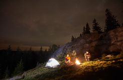 Night summer camping in the mountains under night starry sky. Night camping in the mountains. Young couple hikers having a rest together, sitting beside campfire stock photography