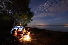 Night summer camping on shore. Group of young tourists around campfire near tent under evening sky. Group of four tourists resting on lake shore at campfire in stock photography