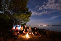Night summer camping on shore. Group of young tourists around campfire near tent under evening sky royalty free stock image