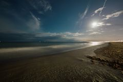 Night summer sand beach with full moon. Seascape Royalty Free Stock Photography