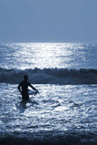 Night-Surfing Under Moon-light. Silhouette of surfer wading into ocean-waves under moonlight Stock Photography
