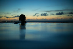Night Swim in Turks and Caicos. A female model is seen in profile silhouette relaxing in an infinity pool at dusk on the Island of Turks and Caicos Royalty Free Stock Images