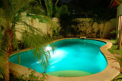 Night swimming pool in tropical garden. Swim swimming pool water garden house Stock Photography