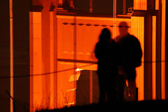 Couple shadow on bridge. Shadow of a man and woman silhouetted on a bridge support at night Royalty Free Stock Images