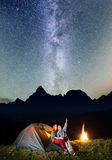 Night tent camping. Family - man and woman sitting near tent and campfire and enjoying incredibly beautiful starry sky. Night tent camping. Charming family - men Stock Image