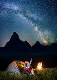 Night tent camping. Happy couple hikers sitting near tent and campfire and enjoying incredibly beautiful starry sky Stock Images