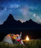 Night tent camping. Pair of tourists sitting near tent and campfire and looking to incredibly beautiful starry sky Stock Images