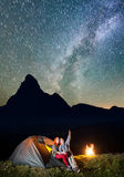 Night tent camping. Romantic couple tourists sitting near tent and campfire and enjoying incredibly beautiful starry sky Stock Photography