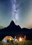 Night tent camping. Tourist couple - girl and guy sitting by bonfire under incredibly beautiful starry sky Stock Image