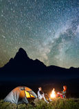 Night tent camping. Tourist family - man and woman sitting by bonfire under incredibly beautiful starry sky stock photo