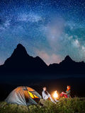 Night tent camping. Young couple backpackers sitting by bonfire under incredibly beautiful starry sky and Milky way Royalty Free Stock Image