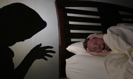 Night terror. Woman in bed screaming with terror as a shadowy intruder approaches, or having a nightmare royalty free stock photo