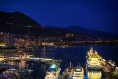 Night time aerial view of the port in Monaco. Warm lights from yachts and Monte Carlo during the evening a couple of hours after sunset Stock Photo