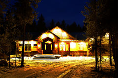 Night Time Cabin in the Woods Wilderness Lights Glowing Warmth Royalty Free Stock Image