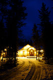 Night Time Cabin in the Woods Wilderness Lights Glowing Warmth Stock Photo