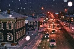 Night time cityscape snow falling cars moving. City evenibg lights winter season traffic royalty free stock photos