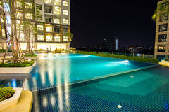 Night time of condominium and swiming pool. Life of City people in modern town Stock Photos
