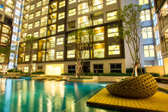 Night time of condominium and swiming pool. Life of City people in modern town Royalty Free Stock Images