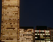 Night time corporations. Symetry of three buildings at night Royalty Free Stock Image