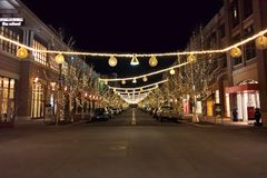 Night time, empty retail street with lights. LAKEWOOD, CO - JANUARY 07, 2018: Quiet, empty street at night with festive holiday lights and decorations at the stock photo