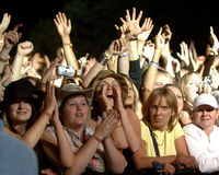 Music festival crowd. Night time at the front of a festival crowd with a young woman calling out and many arms in the air Royalty Free Stock Photos