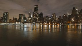 Night time-lapse of Manhattan skyscrapers from water. Wide angle Stock Images