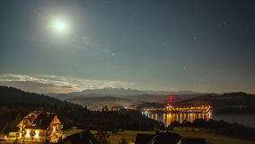 Night Time Lapse with Moon, Stars, Clouds, Mountains and Village near the Lake stock video