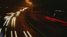 Night time Light Beam Highway. Medium wide high angle time lapse shot at low shutter speed slowly zooming out over cars driving over the freeway at night stock video footage