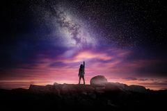 Night Landscape And Milky Way. Night time long exposure landscape photography. A man standing in a high place reaching up in wonder to the Milky Way galaxy Royalty Free Stock Photo
