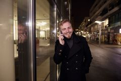 Night time, one young smiling and happy man, 20-29 years, talking over his phone, standing in Autumn coat on street, in front of stock photography