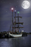 Night time Sail Boat. Sail boat at dock getting ready for a night time sail. Full moon, stars, and lights on boat shine bright Royalty Free Stock Image