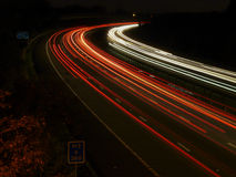 Night time traffic light trails on motorway. Light trails of approaching headlights and receding tail lights on M3 motorway in the UK Stock Photography