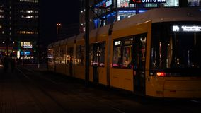 Night time video of trams and people in Alexanderplatz formerly East Berlin, Germany stock footage