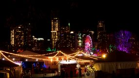 Night time view of a holiday carnival in front of the skyline of downtown Austin, Texas royalty free stock images
