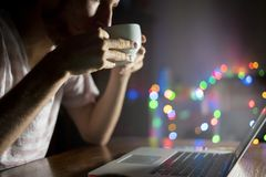 Night time worker in office sitting at the table using laptop and drink coffee f royalty free stock images