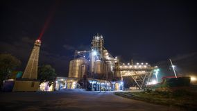Night timelapse of loading grain crops on bulk freighter ship via trunk to open cargo holds at silo terminal in seaport. From above. Cereals bulk transshipment stock video