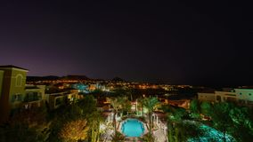 Night to morning timelapse of some building, swimming pool and Lake Las Vegas. Night to morning of some building, swimming pool and Lake Las Vegas with a starry stock video footage
