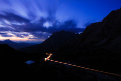 Night Traffic. The road that crosses Valparola Pass at night, Dolomites mountains, Italy royalty free stock photography