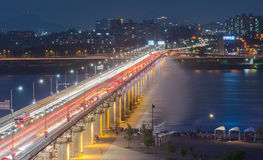 Night traffic blurs past Banpo Bridge Rainbow Fountain in Seoul,. South Korea Royalty Free Stock Images
