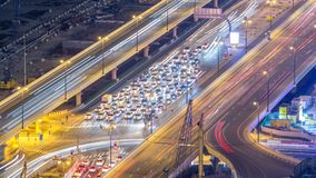Night traffic on a busy intersection at Dubai downtown highway aerial timelapse. View from rooftop near mall stock video footage