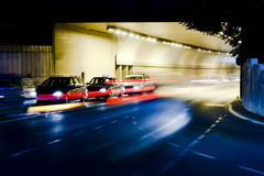 Night traffic on city streets. Cars qued at tunnel exit waiting at intersection while driving vehicles moving past entering the tunnel leaving colored light Stock Photo