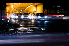 Night traffic on city streets. Cars queued at tunnel exit waiting at intersection while driving vehicles moving past leaving color light trails Stock Photography