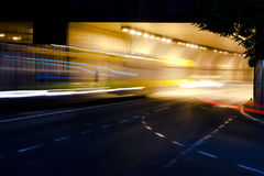 Night traffic on city streets. Vehicles getting in and out of the tunnel Royalty Free Stock Images